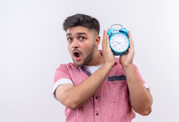 Young handsome guy wearing pink polo shirt holding blue alarm clock warns about being late standing over white wall