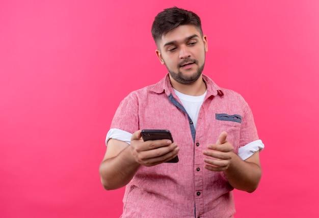 ピンクの壁の上に立っている未定を見下ろしている電話を保持しているピンクのポロシャツを着ている若いハンサムな男