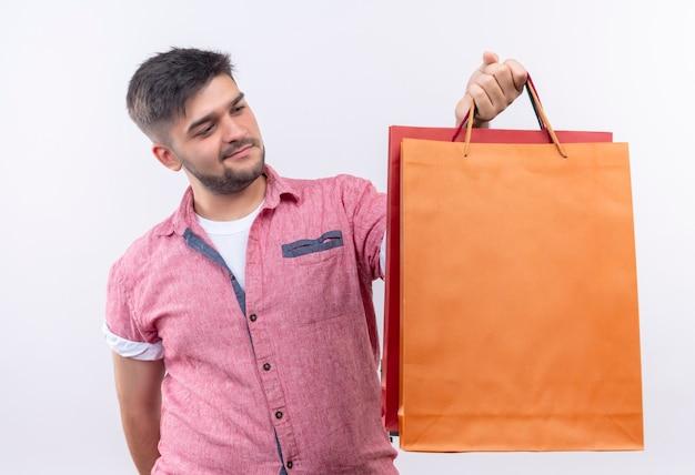 흰 벽 위에 서있는 쇼핑 가방을 들고 분홍색 폴로 셔츠를 입고 젊은 잘 생긴 남자