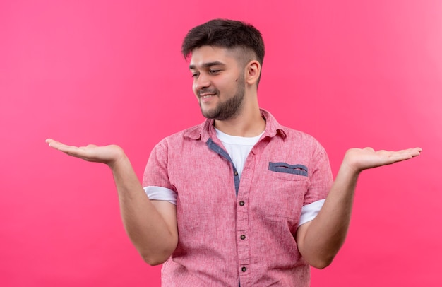 Young handsome guy wearing pink polo shirt holding something in his left and right hands looking at the right hand standing over pink wall