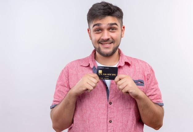 白い壁の上に立っているクレジットカードを喜んで持っているピンクのポロシャツlookinを着ている若いハンサムな男