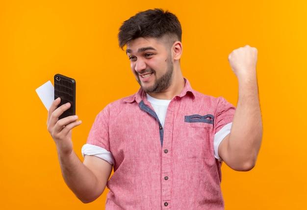 オレンジ色の壁の上に立って勝利を喜んで電話とカードを見てピンクのポロシャツを着た若いハンサムな男