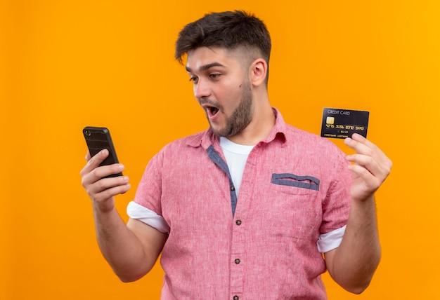 オレンジ色の壁の上に立っているクレジットカードを保持している電話を見ているピンクのポロシャツを着ている若いハンサムな男
