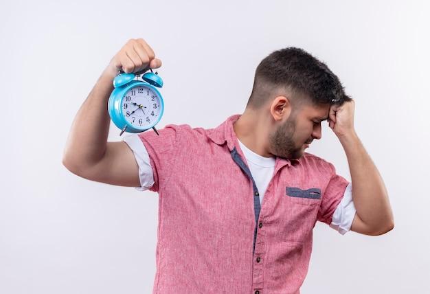 ピンクのポロシャツを着た若いハンサムな男は、白い壁の上に立っている拳で頭を抱えて遅れていることに腹を立てているほかに見ています