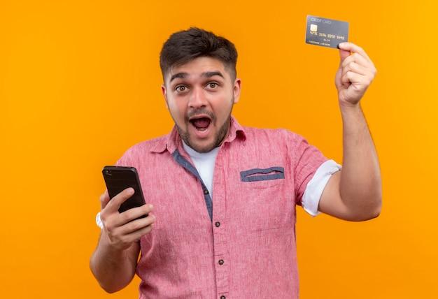 Giovane ragazzo bello che indossa la maglietta di polo rosa che osserva felicemente che tiene il telefono che solleva la carta di credito che sta sopra la parete arancione