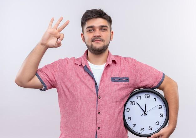 白い壁の上に立っている指でokサインをしている時計を保持しているピンクのポロシャツを着ている若いハンサムな男