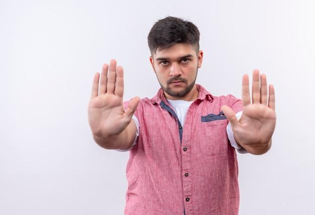 Молодой красивый парень в розовой рубашке поло смотрит серьезно, делает знак остановки с руками, стоящими над белой стеной