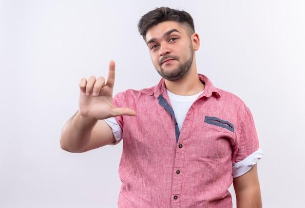 白い壁の上に立っている手で緩いサインを真剣に示しているピンクのポロシャツを着ている若いハンサムな男
