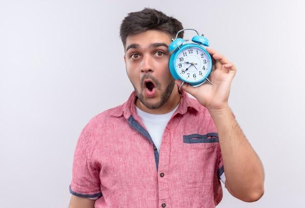 白い壁の上に立っている目覚まし時計を保持してショックを受けたピンクのポロシャツを着ている若いハンサムな男