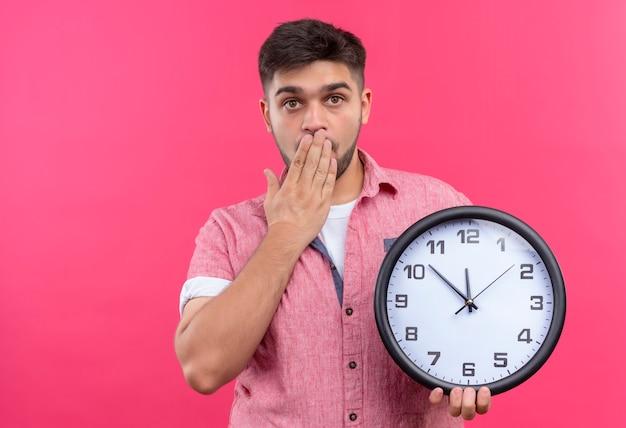 ピンクのポロシャツを着た若いハンサムな男は、ピンクの壁の上に遅れて立っているのを恐れて、ショックを受けた保持時計を探しています