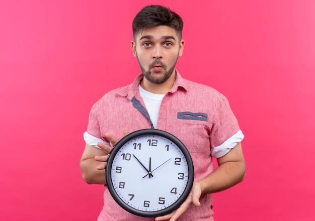ピンクの壁の上に立っている時計を保持して驚いて見えるピンクのポロシャツを着ている若いハンサムな男