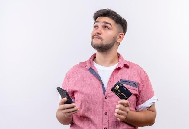 白い壁の上に立っている電話とカードを持って思慮深く見上げるピンクのポロシャツを着ている若いハンサムな男