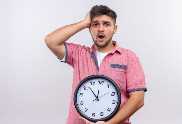 Young handsome guy wearing pink polo shirt looking worried for being late holding clock standing over white wall