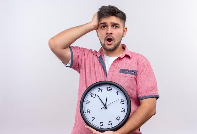 白い壁の上に立っている時計を保持するのが遅くなることを心配しているピンクのポロシャツを着ている若いハンサムな男