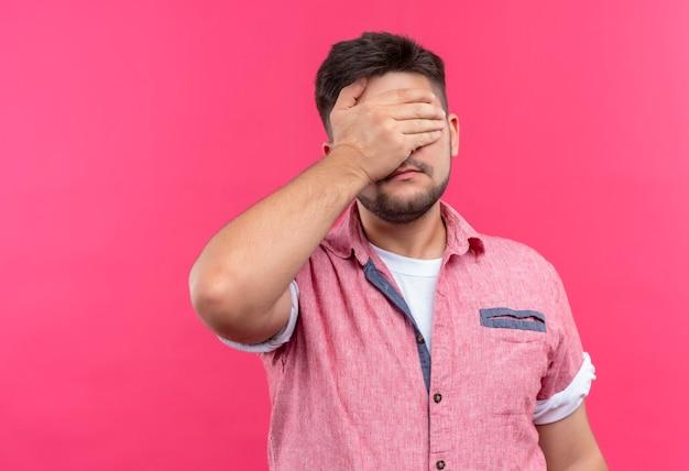 Молодой красивый парень в розовой рубашке поло делает фейспалм, стоя над розовой стеной