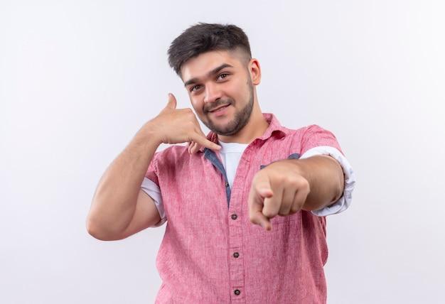 분홍색 폴로 셔츠를 입고 젊은 잘 생긴 남자가 장난스럽게 전화를 걸어 흰 벽 위에 서서 서명