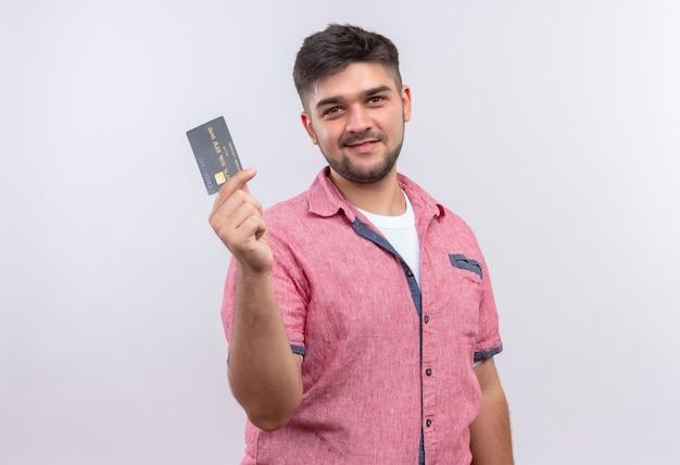 ピンクのポロシャツを着た若いハンサムな男は、白い壁の上に立っているクレジットカードを持って見て喜んでいます