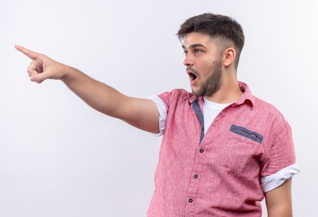 Giovane bel ragazzo che indossa la maglietta polo rosa che punta scioccato a destra con l'indice in piedi sopra il muro bianco