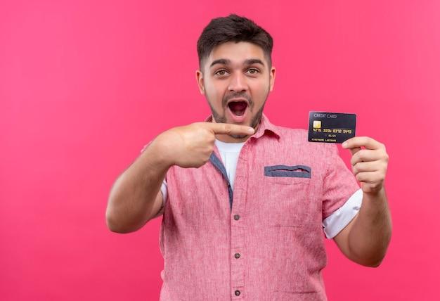 ピンクの壁の上に立って驚いたカードを指しているピンクのポロシャツを着ている若いハンサムな男