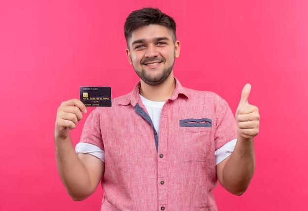 Giovane ragazzo bello che indossa la camicia di polo rosa che elogia la carta di credito con i pollici felici in su in piedi sopra il muro rosa