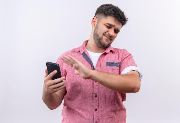 흰 벽 위에 서있는 전화를보고 거부하는 분홍색 폴로 셔츠를 입고 젊은 잘 생긴 남자