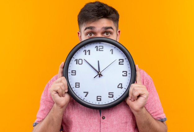 ピンクのポロシャツを着た若いハンサムな男は、オレンジ色の壁の上に遅れて立っているために時計の後ろに隠れて怖がっています