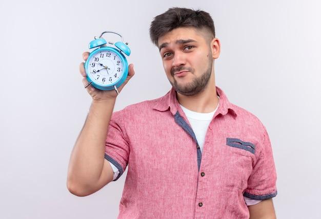 目覚まし時計を示すピンクのポロシャツを着た若いハンサムな男は、白い壁の上に立っている遅い顔です