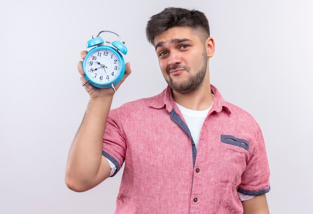 Young handsome guy wearing pink polo shirt showing alarm clock doing you are late face standing over white wall