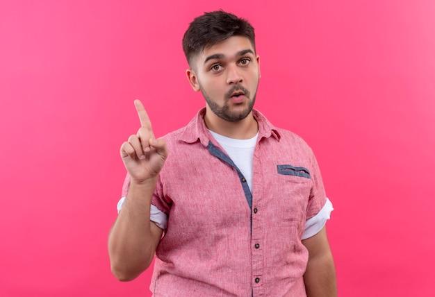 Молодой красивый парень в розовой рубашке поло показывает идею, указывая вверх с указательным пальцем, стоящим над розовой стеной