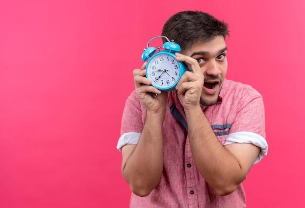 ピンクのポロシャツを着た若いハンサムな男は、ピンクの壁の上に立っている青い目覚まし時計を保持する時間であることを示しています