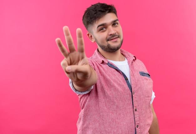 분홍색 벽 위에 서있는 손가락으로 세 개의 기호를 보여주는 분홍색 폴로 셔츠를 입고 젊은 잘 생긴 남자