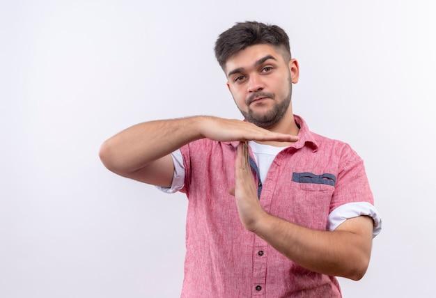 Giovane ragazzo bello che indossa la maglietta polo rosa che mostra il tempo fuori con le mani in piedi sul muro bianco