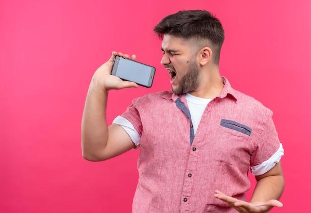 ピンクの壁の上に立って電話で歌うピンクのポロシャツを着た若いハンサムな男