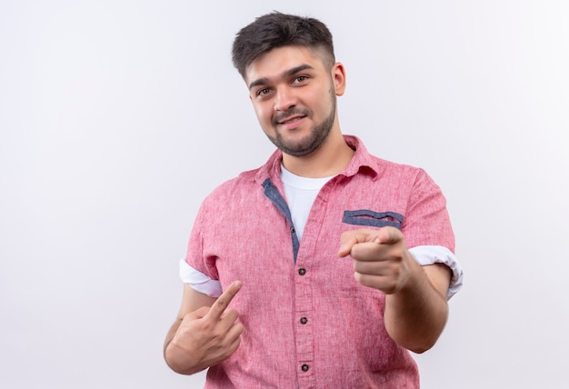 Young handsome guy wearing pink polo shirt smiling pointing with forefingers standing over white wall