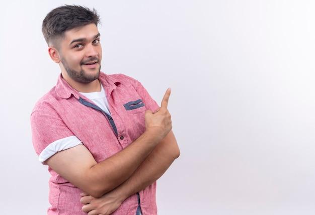 Молодой красивый парень в розовой рубашке поло стоит и указывает указательным пальцем на спину над белой стеной