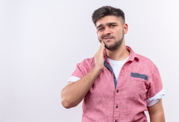 Молодой красивый парень в розовой рубашке поло, страдающий от зубной боли, держится за щеку рукой, стоящей над белой стеной