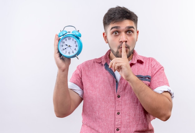 ピンクのポロシャツを着た若いハンサムな男は、白い壁の上に立っている指で沈黙のサインをしている目覚まし時計を持って静かであることについて警告します