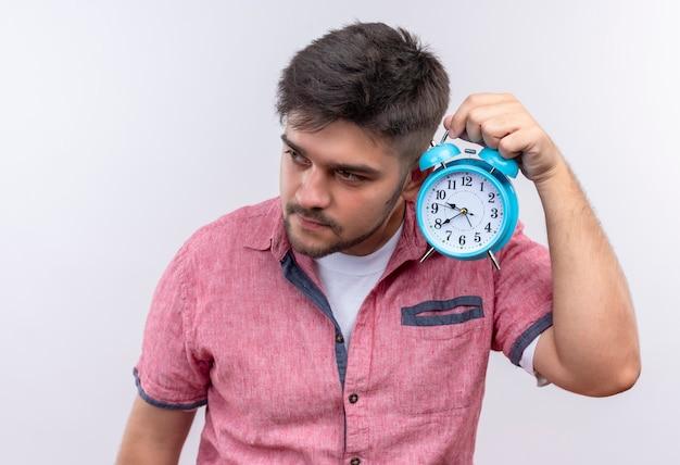 目覚まし時計が白い壁の上に立って働いているかどうか疑問に思っているピンクのポロシャツを着ている若いハンサムな男