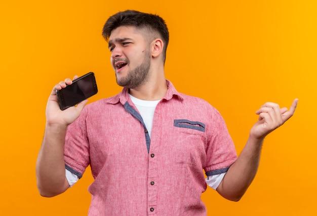 オレンジ色の壁の上に立っている電話シャツでふざけて歌うピンクのポロシャツを着た若いハンサムな男