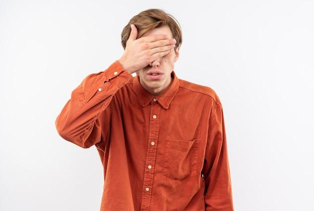 赤いシャツを着た若いハンサムな男は手で目を覆った