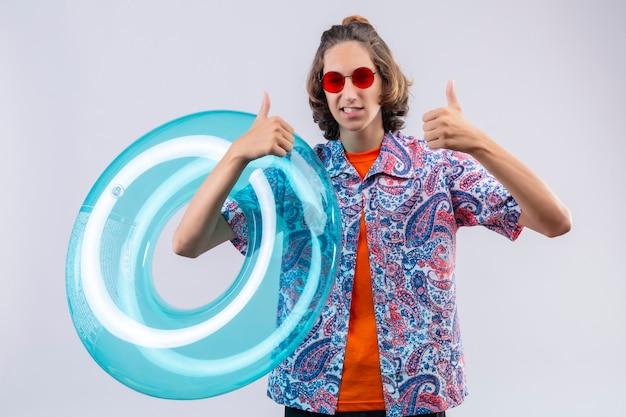 흰색 배경 위에 서 엄지 손가락을 보여주는 웃는 행복 한 얼굴로 카메라를보고 풍선 반지를 들고 빨간 선글라스를 착용하는 젊은 잘 생긴 남자