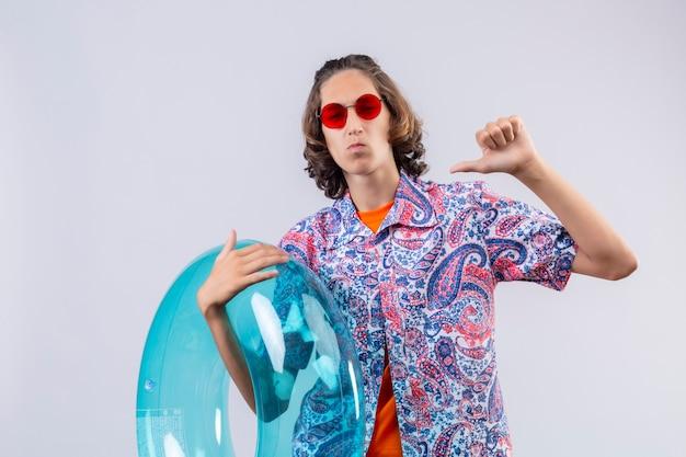 立っている親指で自分を指しているインフレータブルリング自己満足を保持している赤いサングラスをかけている若いハンサムな男