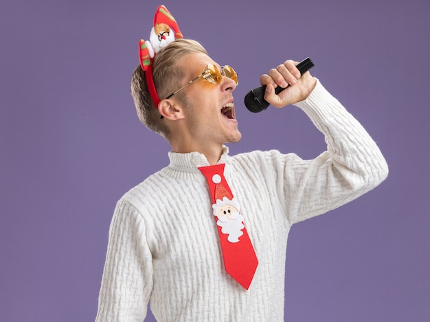 Giovane ragazzo bello che indossa la fascia di babbo natale e cravatta con gli occhiali che tiene il microfono cantando con gli occhi chiusi isolato su sfondo viola con spazio di copia