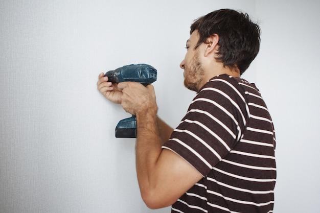 Молодой красивый парень с отверткой сверлит белую стену в новой квартире, делает ремонт.