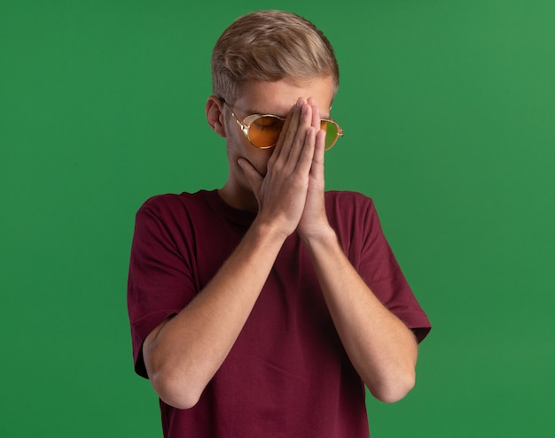 Young handsome guy with closed eyes wearing red shirt and glasses grabbed nose with hands isolated on green wall