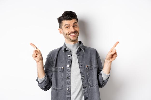 옆으로 손가락을 가리키는 콧수염, 흰색 배경에 캐주얼 옷에 서 카메라에 행복 미소, 두 로고를 보여주는 젊은 잘 생긴 남자.