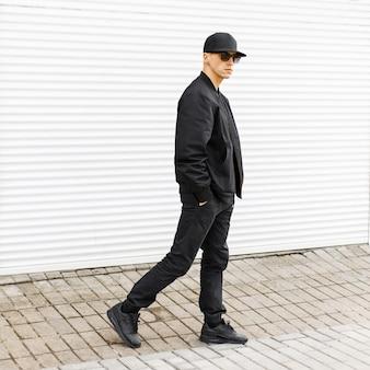 黒の野球帽、ジャケット、ズボン、スニーカーでサングラスをかけた若いハンサムな男