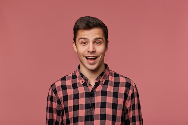 Young handsome happy amazed guy in checkered shirt, looks at the camera with surprised expression, iso;ated over pink background with wide open mouth.