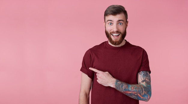 Young handsome happy amazed red bearded man in blank t-shirt, looks surprised, stands over pink background broadly smiling, wants to draw you attention and points to copy space on the left side.