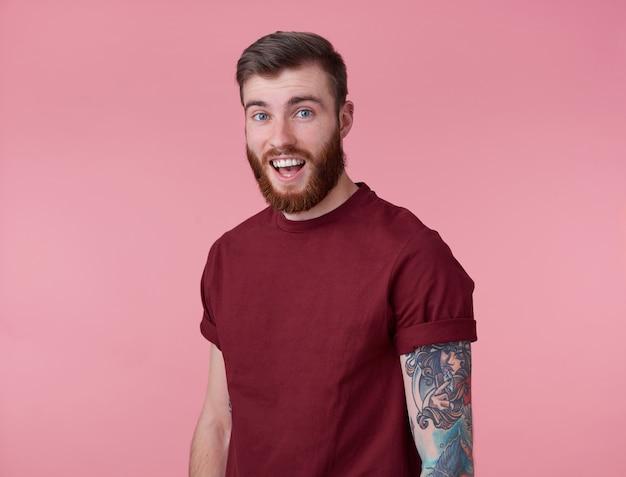 Giovane uomo barbuto rosso stupito felice bello in maglietta vuota, si leva in piedi su sfondo rosa, guarda sorpreso la telecamera con la bocca spalancata e gli occhi.